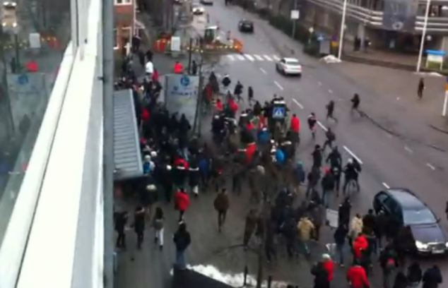 Protesters charge off down the street and later regroup at a shopping mall in central Gothenburg